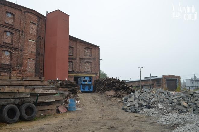 Robotnicy krzątają się wokół starego budynku Huty Silesia