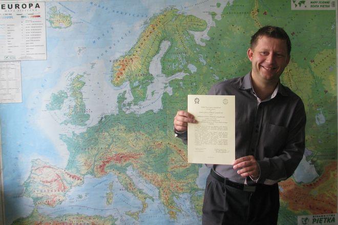 Sławomir Targosz prezentuje list gratulacyjny z Polskiego Towarzystwa Geograficznego