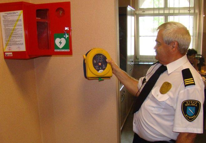 Nowy defibrylator prezentuje strażnik urzędu miasta.